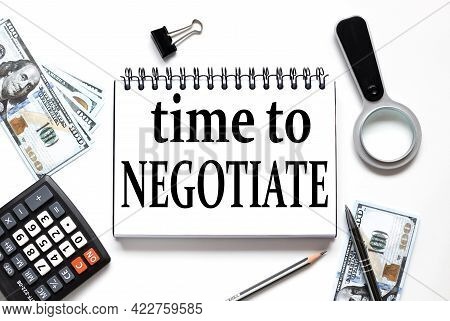 Time To Negotiate. Notebook On White Workspace. Near The Notepad Dollar Bills And A Calculator