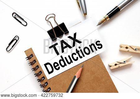Tax Deductions. The Inscription On The Business Card Is Attached To The Notebook.