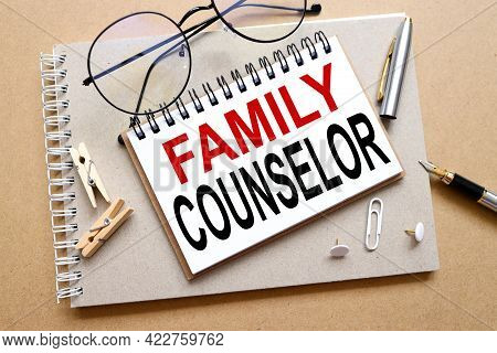 Family Counselor. Text On White Paper On Notepad. On Craft Background