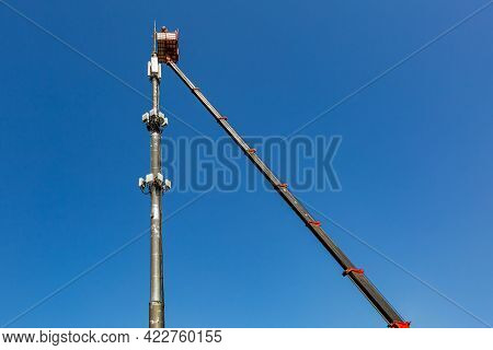 Engineer Is Working On The Telecommunication Tower - Cellular Phone Repeater Mast - From An Aerial W