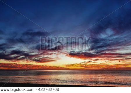 Dramatic Sunset Over The Sea. Dusk. There Are Purple And Scarlet Clouds In The Blue Sky. Orange Glow