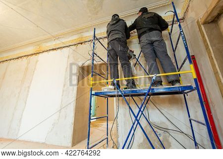 Two Workers Is Installing The Electrical Wires On The Wall That Is The Part Of Internal Wiring In Ap