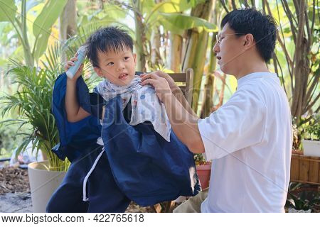 Cute Smiling Asian Kid Young Boy Getting A Haircut At Home Backyard, Father Makes A Haircut For His