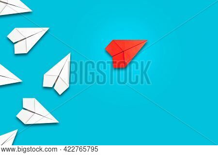 Red Paper Plane Flying In Front Of A Group Of Whites. Blue Background. Copy Space. Leadership Concep
