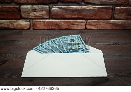 Dollars In One-hundred-dollar Bills Are Spread Out In An Envelope On A Table Near The Brick Wall. Do