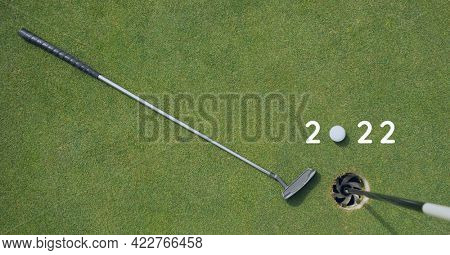 Composition of 2022 number with golf ball and golf club on golf course. sports calendar and competition concept digitally generated image.