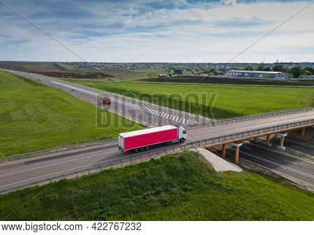 Pink Truck with Cargo Semi Trailer Moving on Road in Direction. Highway intersection junction. Aerial Top View