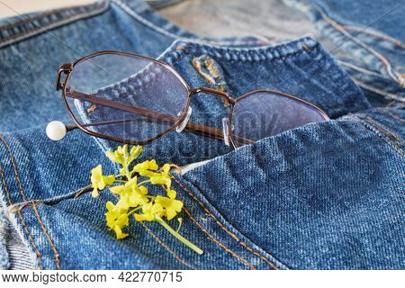 Eyes Glasses And Yellow Wildflowers In The Pocket Of A Blue Denim Jacket, Trend Eyes Glasses