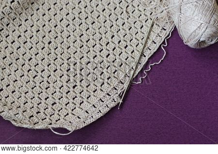 Crocheting With Beige Cotton Threads On A Purple Background.