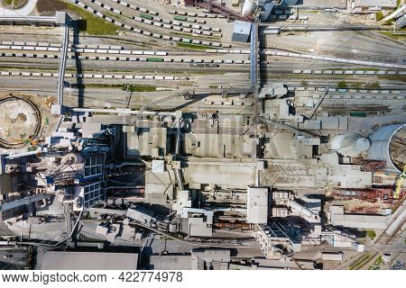 Aerial View Of Cement Plant With High Concrete Factory Structure And Tower Crane At Industrial Produ