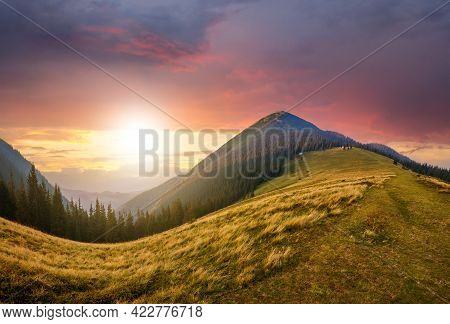 Beautiful View Of Green Grassy Hills At The Foot Of Magnificent Distant Mountain On Bright Sunny Sum