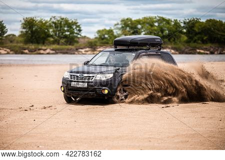 Nikolaevka, Russia - June 23, 2020: Black Subaru Forester Moving On Sand Beach, Sand Flying From Und
