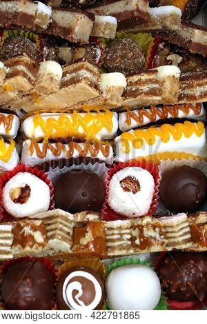Background Of Large Piles Of Sweet Cake Pieces In Different Tastes And Colorful Shapes