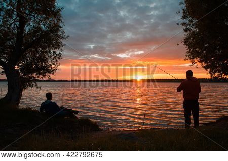 Outdoor Activities. Silhouette Of A Fisherman And His Friend On The Lake At Sunset. Man Resting On T