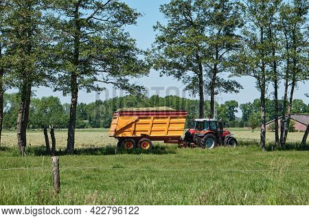 Tractor With Silage Trailer, Freshly Mown Grassland And Road With Trees . Farm In The Background And