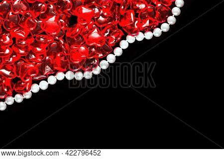 Lots Of Translucent Red Hearts And A String Of White Pearls On A Black Background. Background Frame