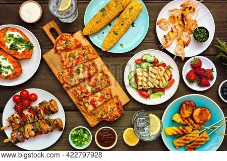 Summer Bbq Grill Table Scene Over A Dark Wood Background. Grilled Flatbread, Chicken And Shrimp Skew