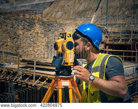 Land Surveyor Stands By Theodolite On A Tripod Against Construction Site At Background. Topographer
