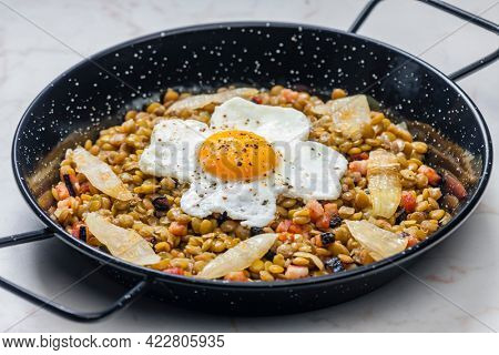 lentils with smoked meat and onion served with fried egg