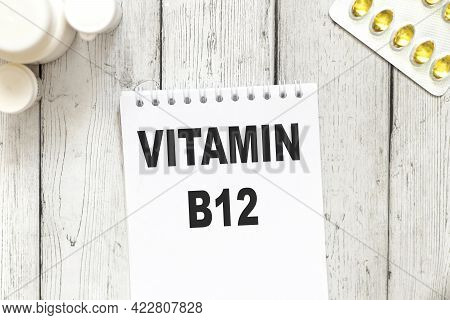 Vitamin B12, Text On White Notepad Paper On Wooden Table Background Near Capsules And Tablets