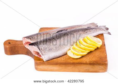 Two split trouts with a lemon ready to be cooked on a cooking board isolated on white poster