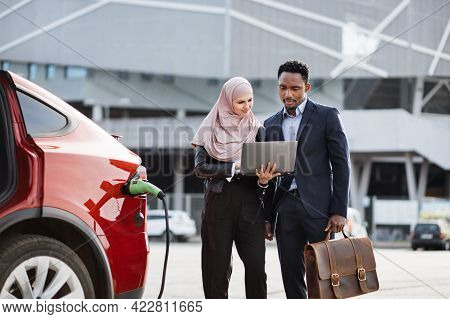 Muslim Woman In Hijab Holding Wireless Laptop And Showing Something To African Man In Business Suit.