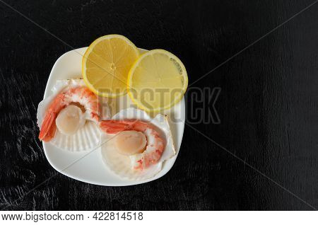 Boiled Shrimp Tails In A Ceramic Bowl With A Raw Scallop In The Shell And Lemon On A Dark Wooden Bac