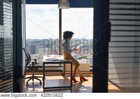 Young Successful Female African American Executive Manager Ceo Sitting On Desk Reading Financial Rep