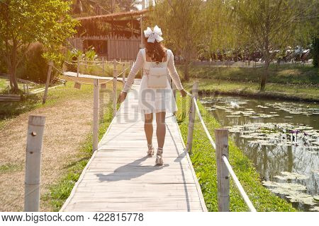 A Beautiful Asian Woman Walks On A Pathway Through A Bridge. To Get To The Buildings In The Park.