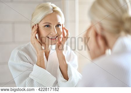 Gorgeous Mid Age Adult 50 Years Old Blonde Woman Standing In Bathroom After Shower Touching Face, Lo