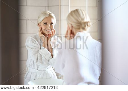 Gorgeous Mid Age Adult 50 Years Old Blonde Woman Standing In Bathroom Wearing Bathrobe Touching Face