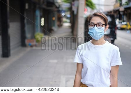 Woman Wearing Medical Face Mask During Walking In Street Footpath And Night Market, Prevent Coronavi