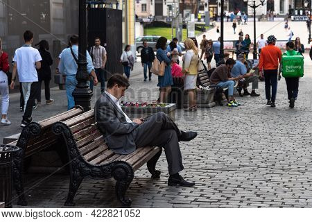 Moscow, Russia, July 27, 2020 - Ordinary City Life, A Man Sits On A Bench And Looks Into A Smartphon
