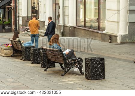 Moscow, Russia, July 27, 2020 - Ordinary City Life, Young Women Sit On Benches And Look Into A Noteb