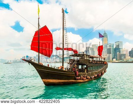 Traditional Wooden Sailboat Or Junk Boat With Red Sails In The Victoria Harbor, Hong Kong