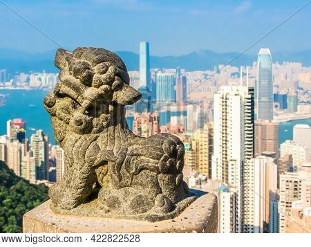 Old Stone Lion On The Victoria Peak And View On The Hong Kong Skyscrapers