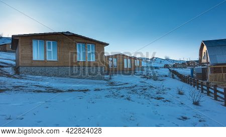 Tourist Base In Siberia. On The Snow-covered Hills, There Are Wooden Cottages With Double-glazed Win