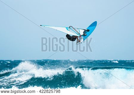 Aquatic Sports: Windsurfer Jumping On The Waves During The Summer