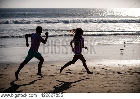 Sport And Healthy Lifestyle, Friends Jogging At Sunset On The Beach. Silhouette Couple Running On Be