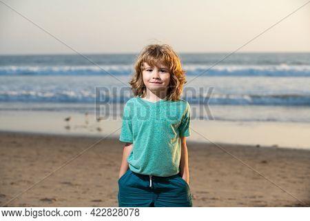 Cute Kid Boy Walking The Sea Beach With Hand In Pocket.
