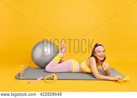 Determined Cheerful Asian Woman With Tired Glad Expression Lies On Fitness Mat Surrounded By Sport E