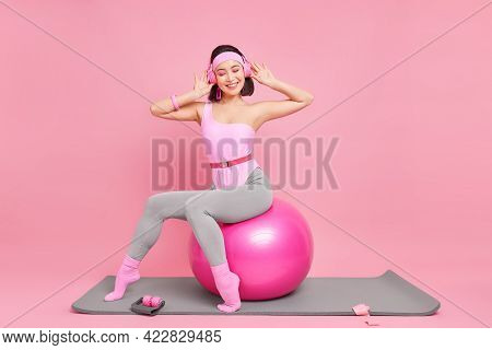 Indoor Shot Of Pleased Asian Woman Has Slim Figure Does Yoga Exercises With Fiss Ball Dressed In Spo