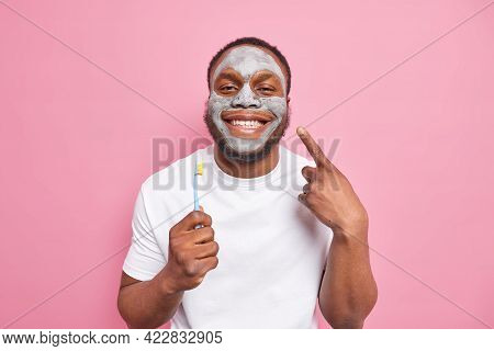 Glad Afro American Man Smiles Happily Cares About Teeth Holds Toothbrush Applies Beauty Clay Mask On