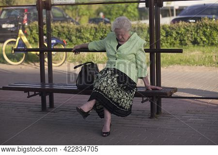 A Beautiful Elegant Elderly Woman Is Tired, Fell Asleep, Sits At A Public Transport Stop In Summer.