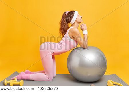Horizontal Shot Of Slim Sporty Woman Leans At Fitness Ball Poses On Mat Does Exercises With Dumbbell