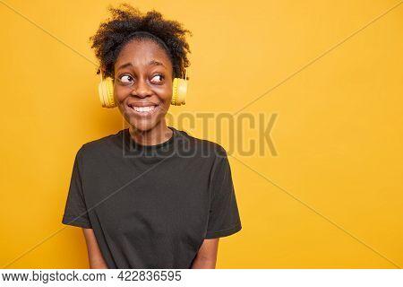 Glad Dark Skinned Woman Smiles Happily Looks Away Wears Headphones On Ears Dressed In Black T Shirt