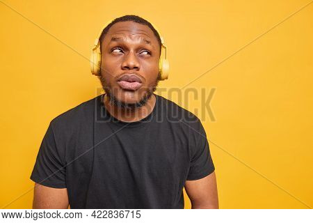 Horizontal Shot Of Handsome Bearded Adult Man Focused Above With Pensive Expression Listens Music Vi