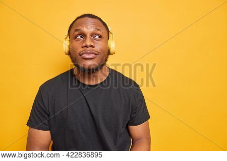 Horizontal Shot Of Thoughtful Black Man Focused Above Dressed In Casual T Shirt Listens Music Via He