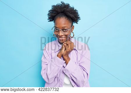Photo Of Nice Looking Dark Skinned Woman Keeps Hands Together Feels Glad And Shy Accepts Compliment