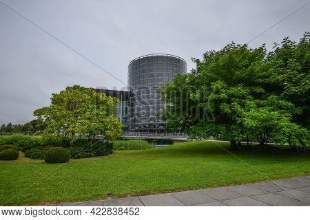 Germany Dresden - August 2015: Panorama Of The Glass Building Of The Volkswagen Plant, Greenery Near